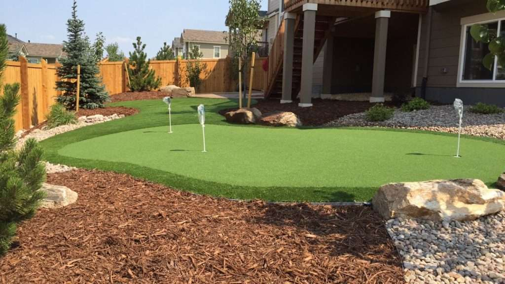Putting green in back yard with 3 holes and flag poles in each hole. Brown mulch and rocks as well.