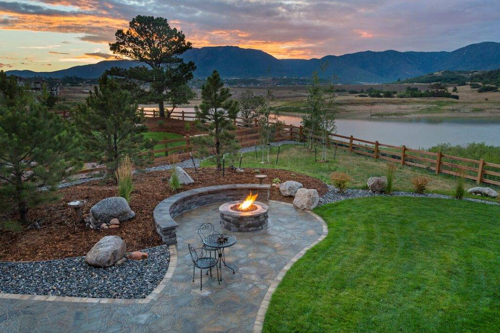 Scenic picture of Colorado sunset with fire pit on stamped concrete and benches close by.